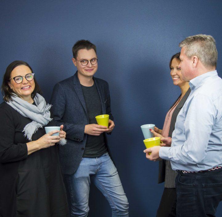 Neljä ihmistä verkostoituu ringissä kahvikupit käsissään