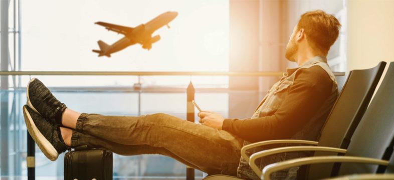Matkustaja lentokentällä ja lentokone ilmassa.